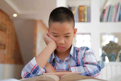 istock asian kid boy child stressed tired frustrated bored from studying. children with unhappy expression. 1071310852