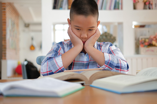 istock asian kid boy child stressed tired frustrated bored from studying. children with unhappy expression. 1071573938