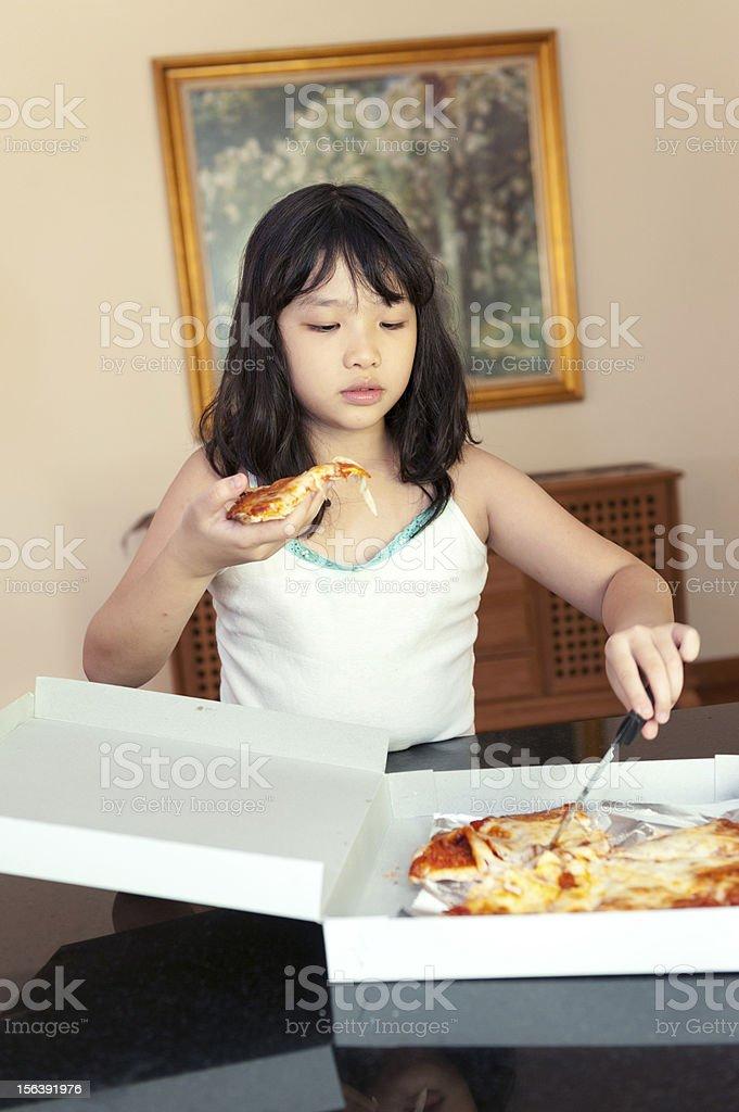 Asian kid eating pizza royalty-free stock photo