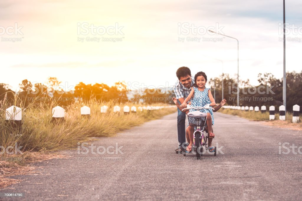 Asian kid girl having fun to ride bicycle with father help to pushing them together stock photo