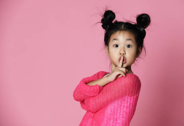 Asian kid girl in pink sweater shows shh sign Close up portrait Asian kid girl in pink sweater shows shh sign on pink background. Close up portrait silence stock pictures, royalty-free photos & images
