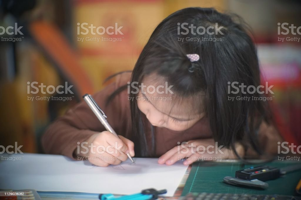 asian kid hands writing in a notebook stock photo