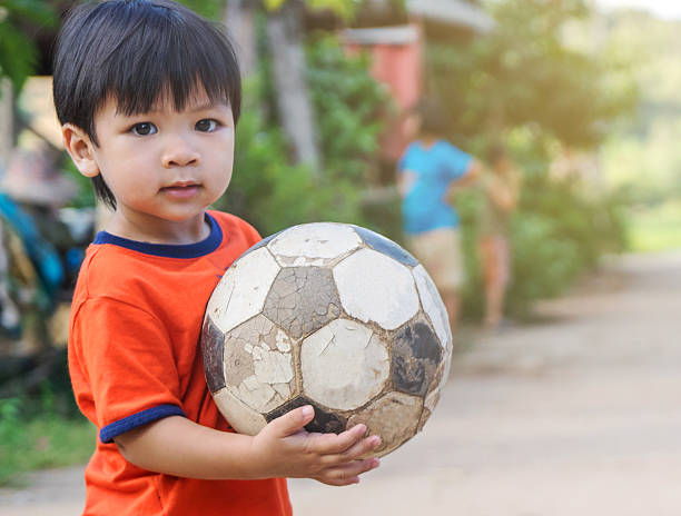 Asian kid in poor village playing old soccer ball stock photo