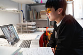 Chinese teenager studying from home during covid-19 quarantine wearing computer glasses