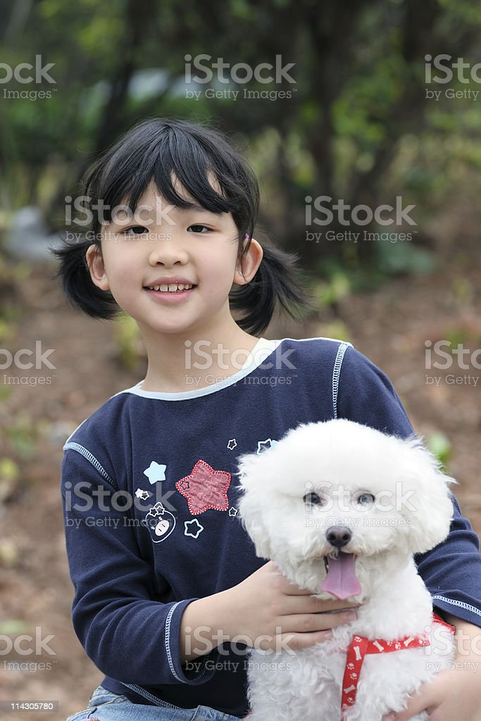 Asian kid playing with dog stock photo