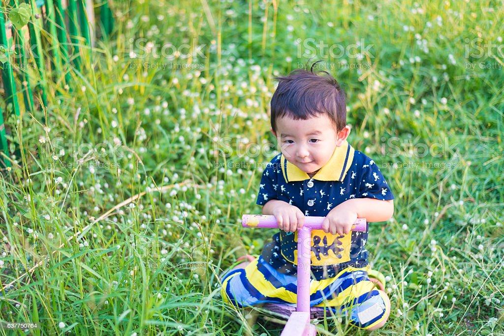 Asian kid riding seesaw board at the playground under sunlight, stock photo