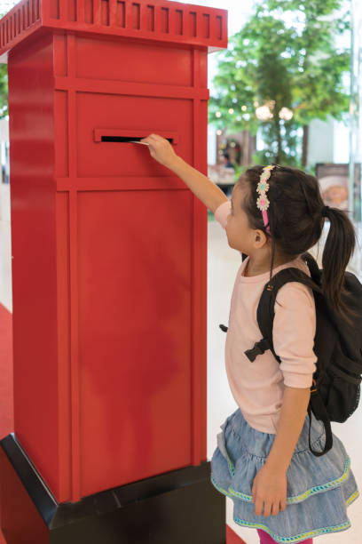 asiatische kind senden ihre mail in den roten briefkasten im einkaufszentrum - arbeiten von schülern aufhängen stock-fotos und bilder