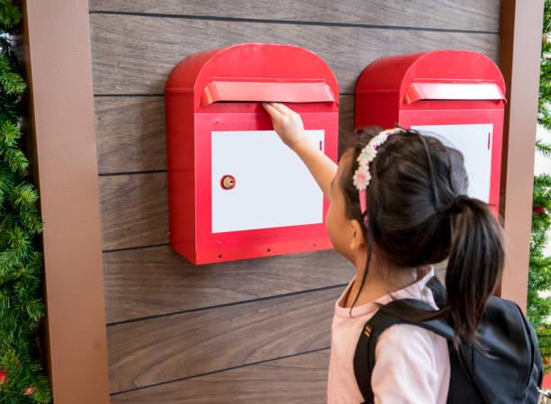 asiatische kinder ihre e-mail in das rote metall postfach an holz wand hängen - arbeiten von schülern aufhängen stock-fotos und bilder