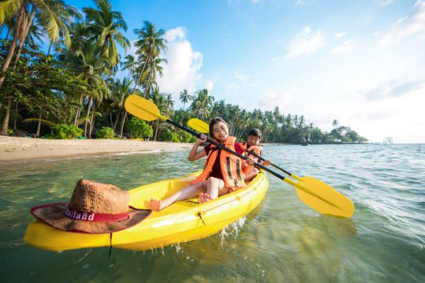 criança asiática para jogar o caiaque na praia em koh kood e koh mak, koh kood e koh mak é ilha no mar da tailândia - esporte aquático - fotografias e filmes do acervo