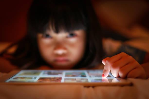 Asian kid using internet tablet screen. stock photo