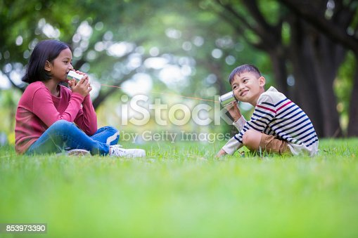 istock asian kids brother playing canned phone in the park 853973390