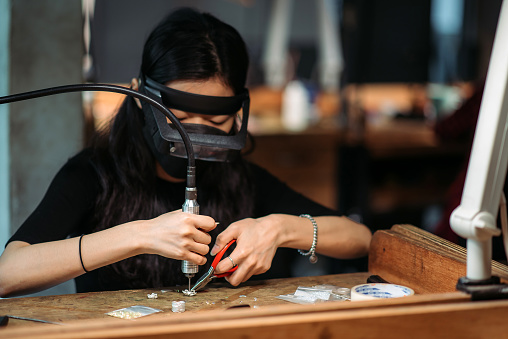 using flexible drill machine for handmade jewelry with wearing specialist magnifying glass