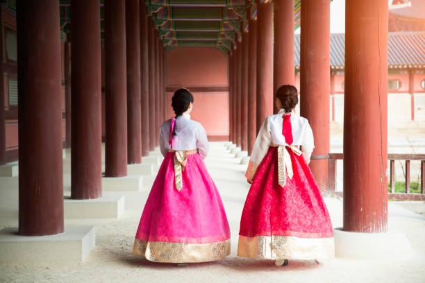 Asian Korean woman dressed Hanbok in traditional dress walking in Gyeongbokgung Palace in Seoul, South Korea. stock photo