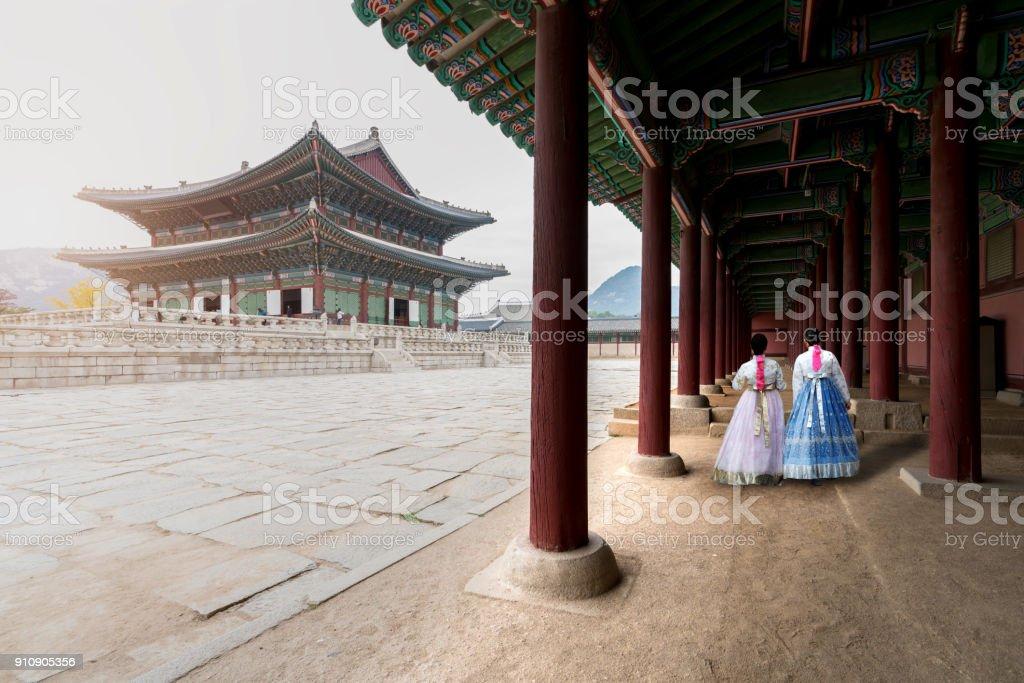 Asian Korean woman dressed Hanbok in traditional dress walking in Gyeongbokgung Palace in Seoul, South Korea. stock photo