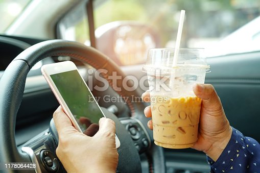 Asian lady holding ice coffee and mobile phone at car to communication with friends in happy hot holiday.