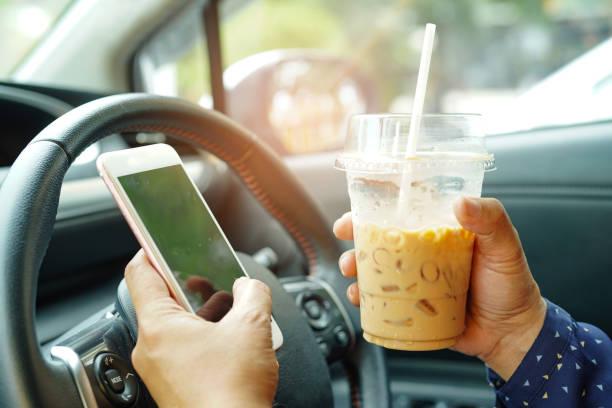 mujer asiática sosteniendo café helado y teléfono móvil en el coche a la comunicación con los amigos en las felices vacaciones calientes. - conducir fotografías e imágenes de stock