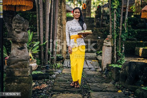 One woman, young lady in traditional Balinese clothing standing outdoors, holding a plate with flowers.