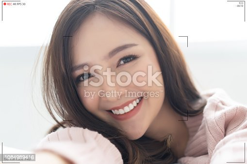 istock Asian lady make selfie recording video vlog from hands with mirrorless camera.  Camera screen of portrait of Asian girl wearing knitted sweater pink cold volgging talking on live stream at white room her house.Concept Photographer live streaming. 1084989416