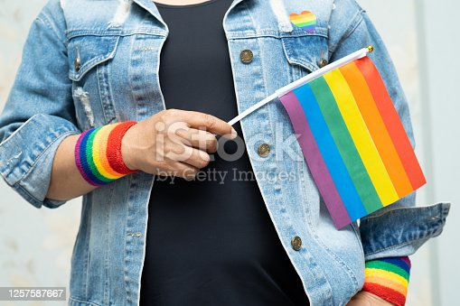 Asian lady wearing blue jean jacket or denim shirt and holding rainbow color flag, symbol of LGBT pride month celebrate annual in June social of gay, lesbian, bisexual, transgender, human rights.