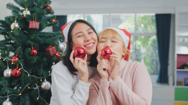 アジアのレズビアンのカップルはクリスマスフェスティバルを祝います。lgbtq女性ティーンは、リラックスハッピープレイクリスマスボールは、自宅のリビングルームで一緒にクリスマス冬� - lgbtqi  ストックフォトと画像
