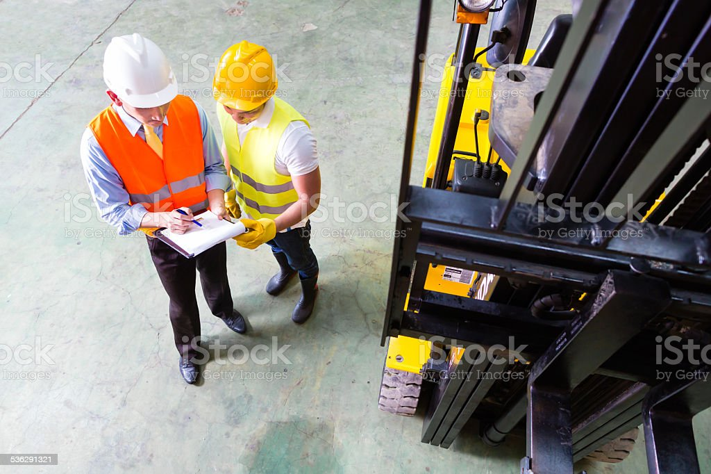 Asian lift truck driver and foreman in storage Asian fork lift truck driver discussing checklist with foreman in warehouse 2015 Stock Photo