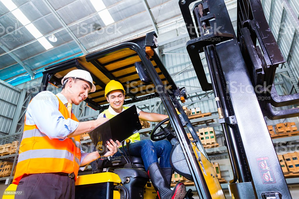 Asian lift truck driver and foreman in storage stock photo