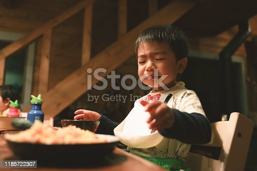 Asian little boy is trying to eat his hates eating
