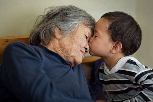 Asian little boy kissing grandmother Asian little boy kissing grandmother korean ethnicity stock pictures, royalty-free photos & images
