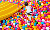 Asian little boy playing in a ball pool.