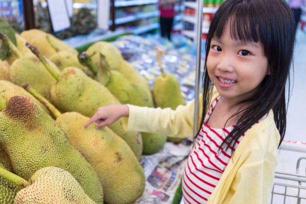 asiatische chinesische mädchen auswahl obst - jackfrucht stock-fotos und bilder