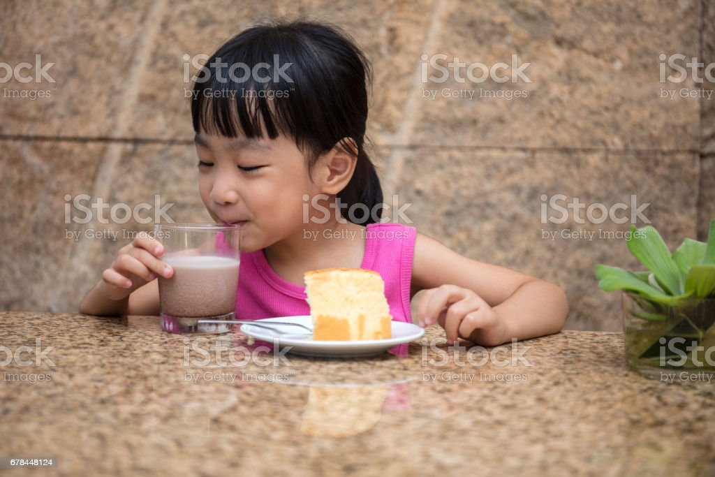 Asian little Chinese girl eating delicious cake royalty-free stock photo