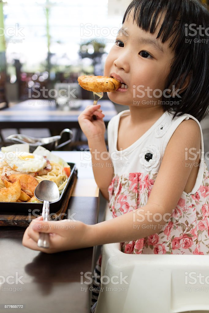 Asian Little Chinese Girl Eating Western Food stock photo