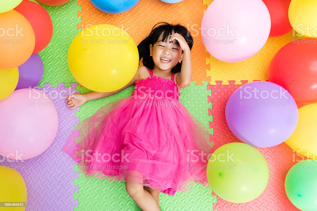 Asian Little Chinese Girl Lying on Floor amongst Balloons stock photo