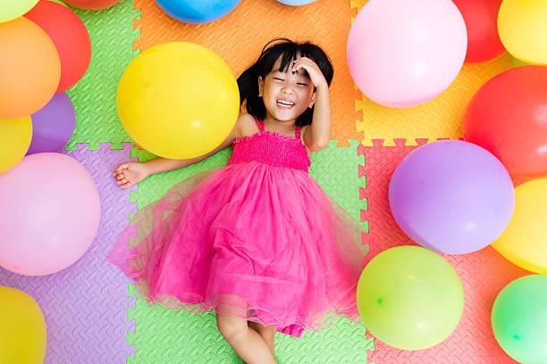 asian little chinese girl lying on floor amongst balloons - kinderparty spiele stock-fotos und bilder
