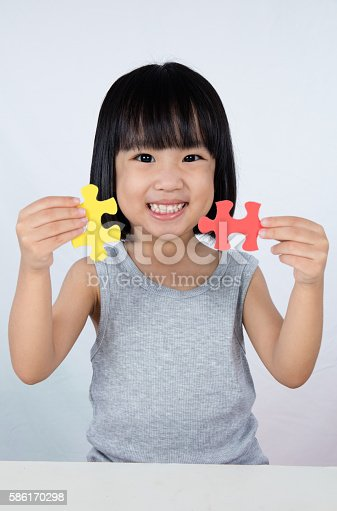 istock Asian Little Chinese Girl Playing Colorful Puzzle 586170298