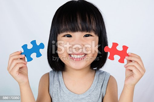 istock Asian Little Chinese Girl Playing Colorful Puzzle 586170350