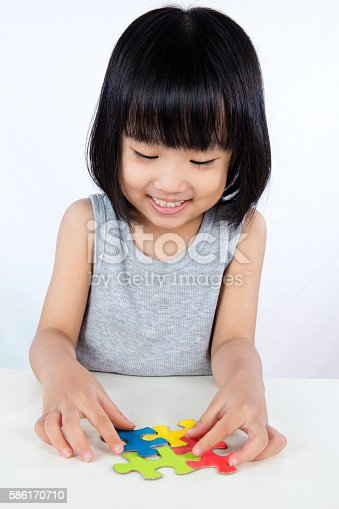 istock Asian Little Chinese Girl Playing Colorful Puzzle 586170710