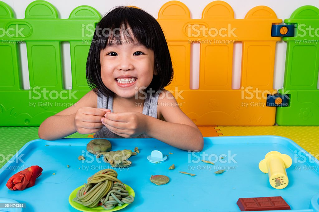 Asian Little Chinese Girl Playing with Colorful Clay stock photo