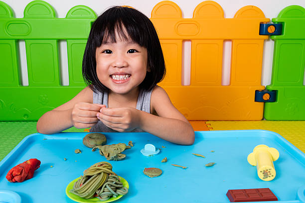 asian little chinese girl playing with colorful clay - knete spiele stock-fotos und bilder