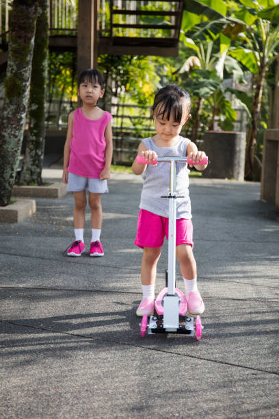Asian little Chinese girls arguing to play the scooter stock photo