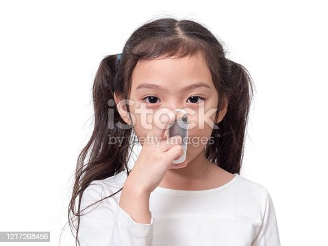 Asian little cute girl 6 years old using asthma inhaler on white background.