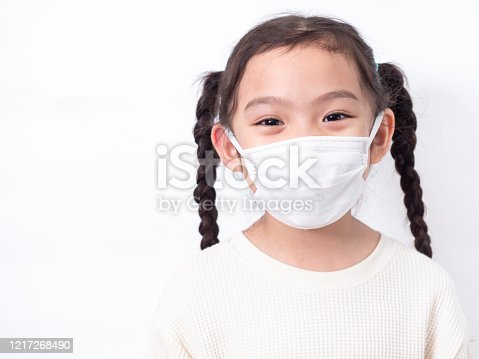 Asian little cute girl 6 years old wearing a hygienic face mask to protective spread the disease on white background. Prevention of spreading the coronavirus COVID-19 cold flu or pollution.