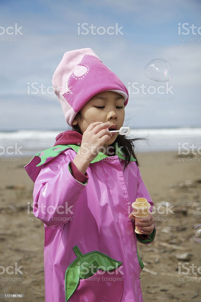 Asian Little Girl Blowing Bubbles at Oregon Coast Beach royalty-free stock photo