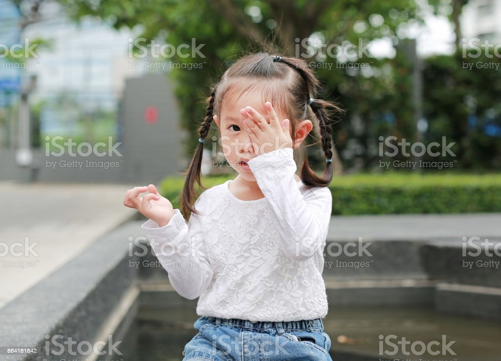 Asian little girl cover her eye with her hand. royalty-free stock photo