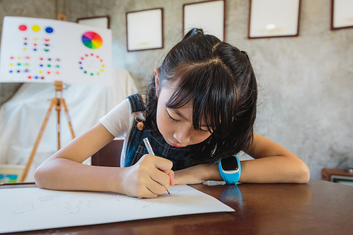 Asian Little girl drawing with pencils on paper at elementary school, Back to school and education concept