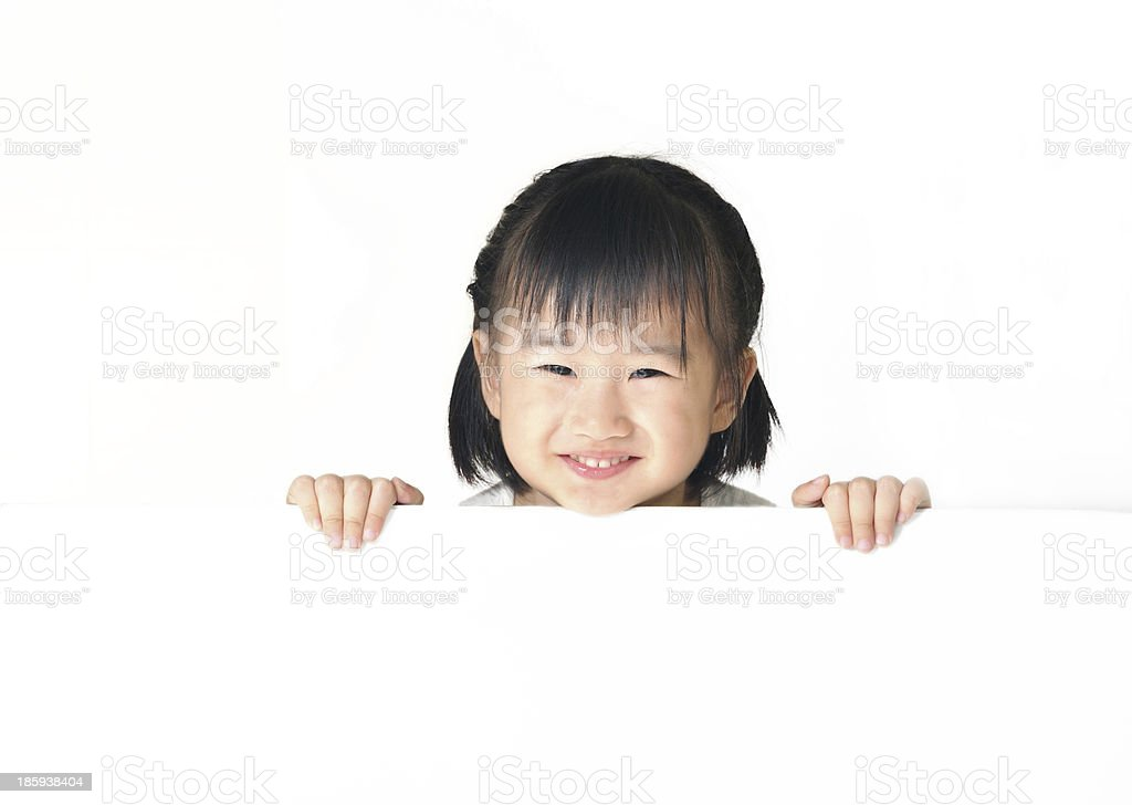 Asian little girl hiding behind white board royalty-free stock photo