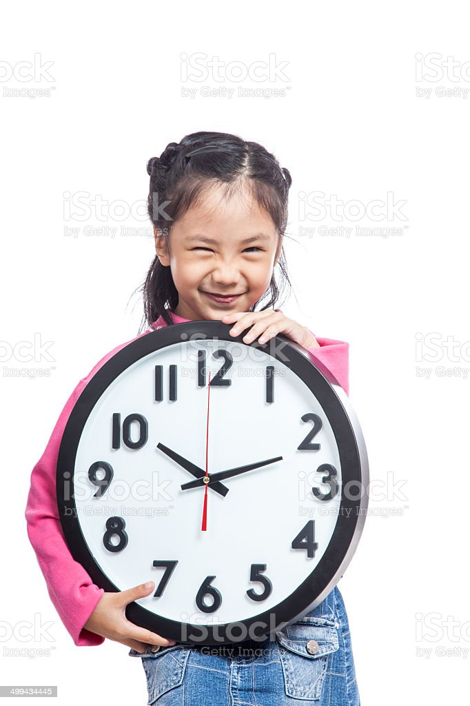 Asian little girl hold a clock and laughing stock photo