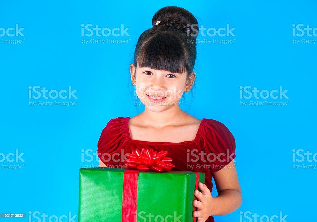 Asian little girl holding big Christmas gift box. stock photo