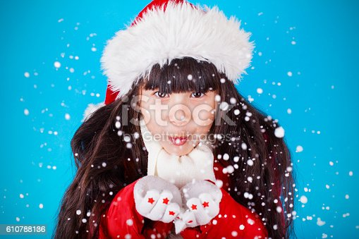 istock Asian little girl in Santa Claus hat blowing snowflakes 610788136