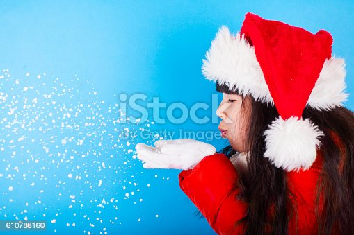 istock Asian little girl in Santa Claus hat blowing snowflakes 610788160
